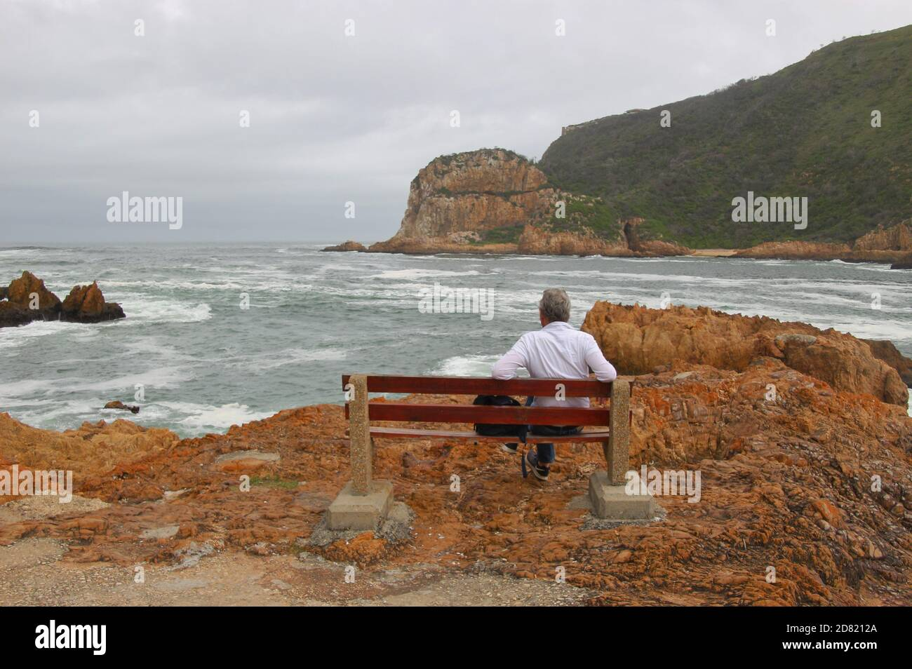 A man sits on a bench, looking at the sandstone cliffs of Knysna Heads. A famous landmark along the renowned Garden Route, South Africa, Africa. Stock Photo