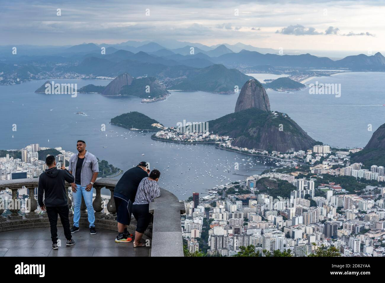 Beautiful view to tourists enjoying the city view from Christ the Redeemer Statue, Tijuca Forest, Rio de Janeiro, Brazil Stock Photo
