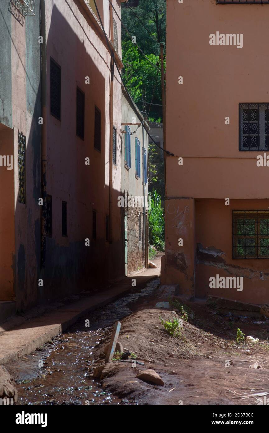 Narrow street with simple plastered colored houses in Setti Fatma in the Ourika Valley near Marrakech, Morocco. The muddy water from the mountains run Stock Photo