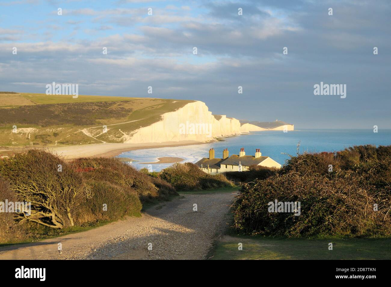 Seven Sisters cliffs and coastguard cottages with Belle Tout Lighthouse in distance, Seaford Head, South Downs National Park, East Sussex, England, UK Stock Photo