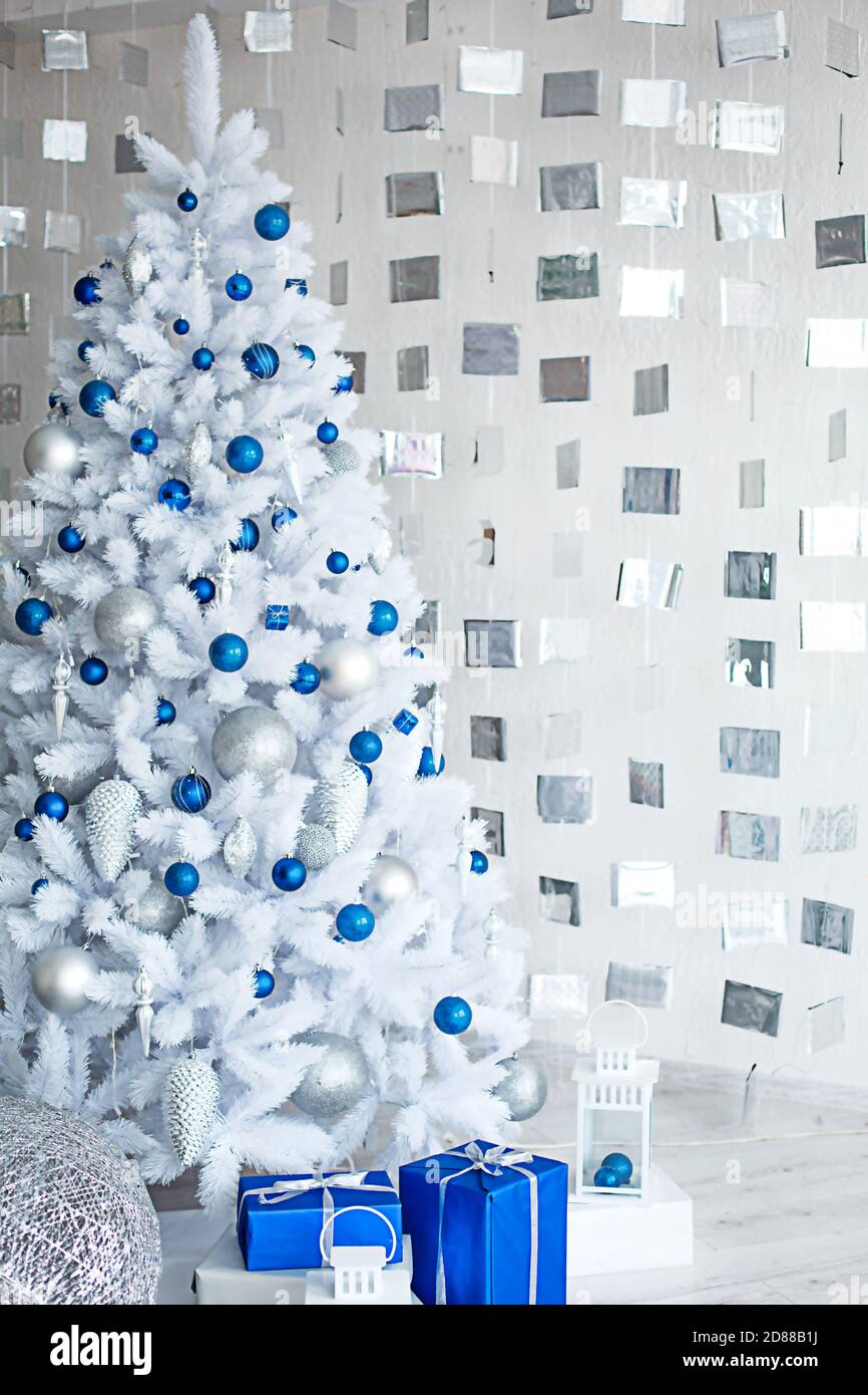 Christmas White Artificial Fir Tree In A Light Gray Room Is Decorated With Blue And Silver Balloons Boxes With Gifts Decorations Made Of Cubes On Th Stock Photo Alamy