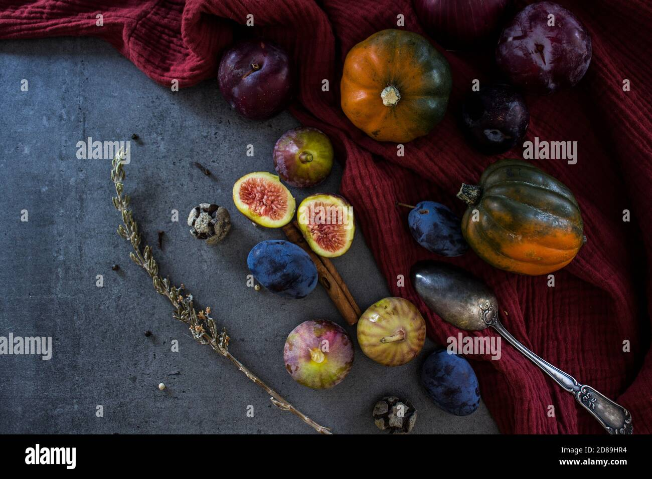Fresh fruits and vegetables on a table. Top view photo of grapes, pumpkins, plums and figs. Grey textured background. Autumn still life. Stock Photo