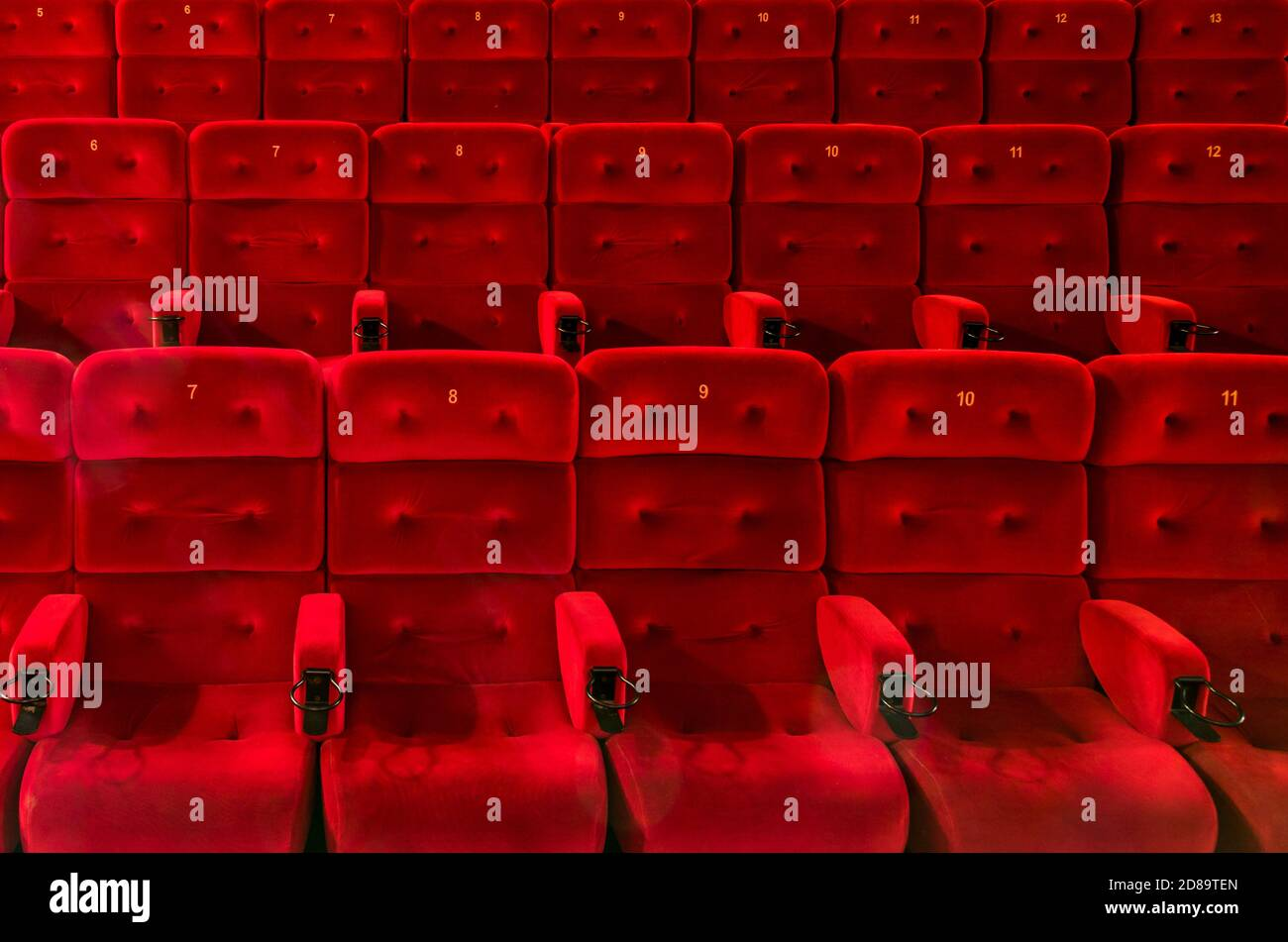 Empty comfortable red seats with numbers in the hall of the cinema or theate Stock Photo