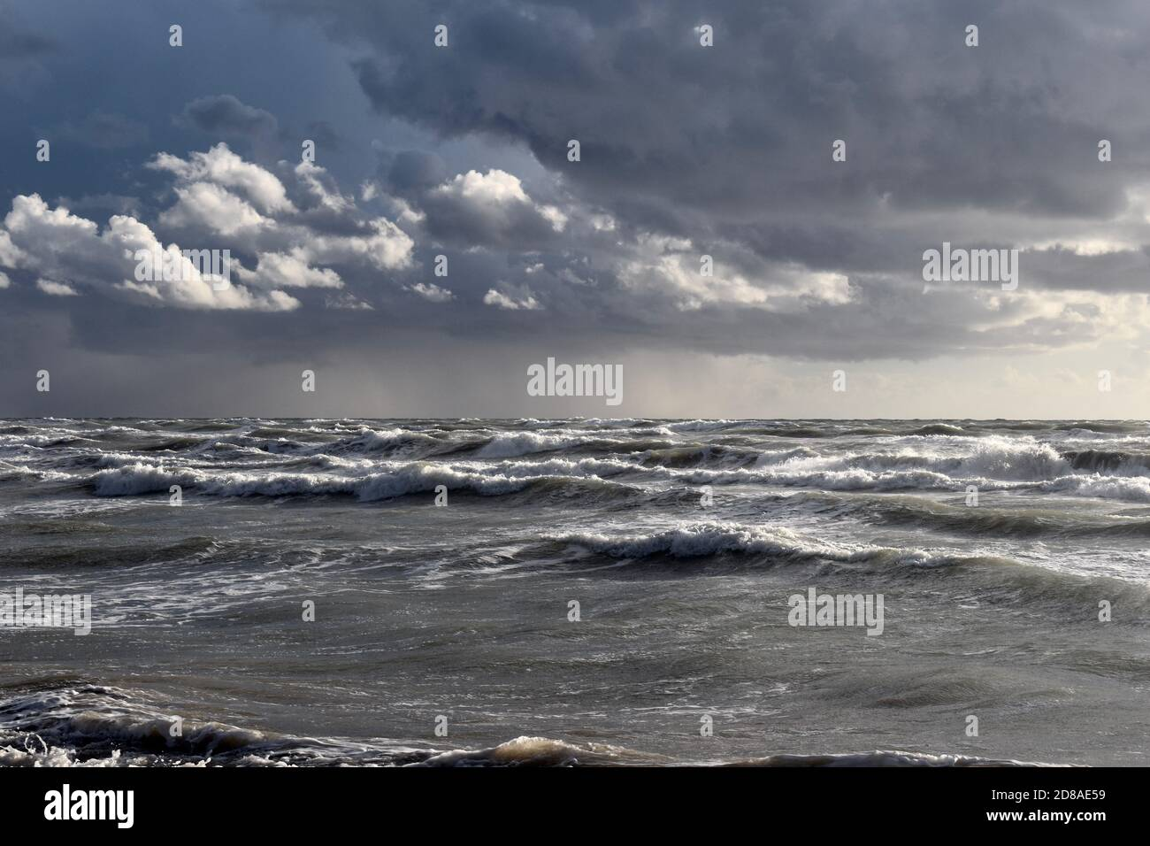 Severe stormy weather on the Tyrrenian sea. Big waves. Grey and deep blue colors. Sky overcast with greyish clouds. Stock Photo