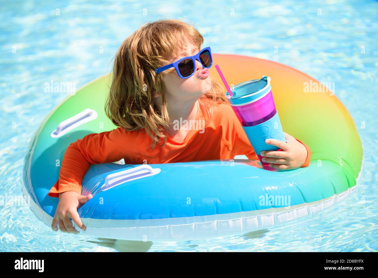 Summer child cocktail party in watter pool in the summer. Little boy relax and swimming in swimming pool with flotation ring on summer. Water toys and Stock Photo