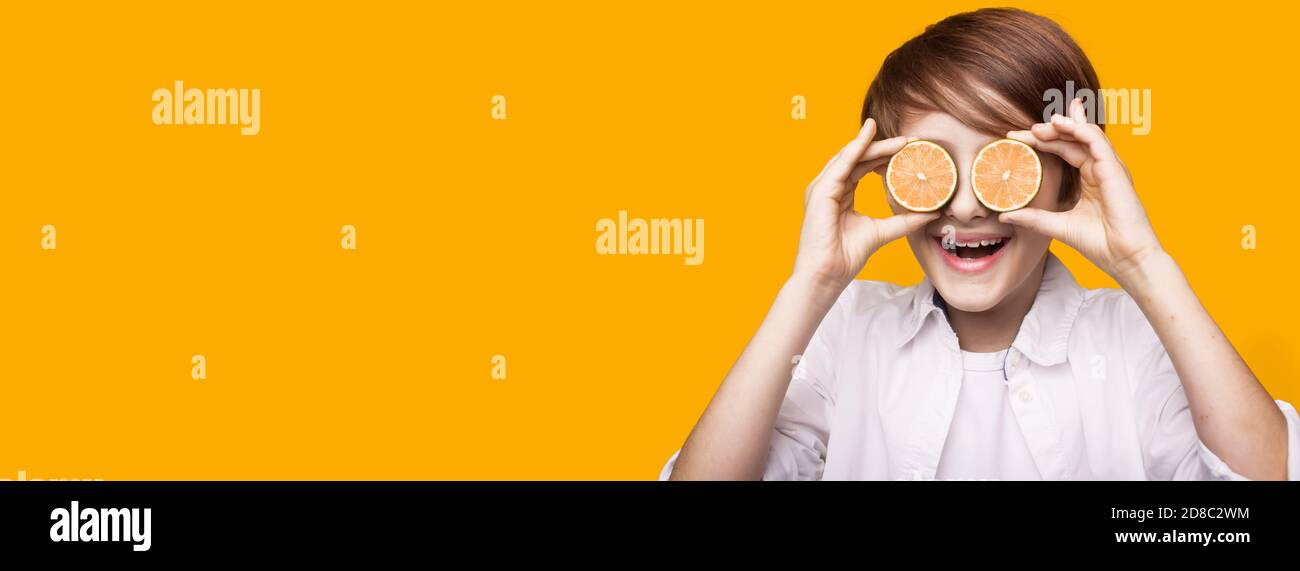 Smiling caucasian boy is covering his eye with sliced lemon pieces posing on a yellow wall with free space Stock Photo