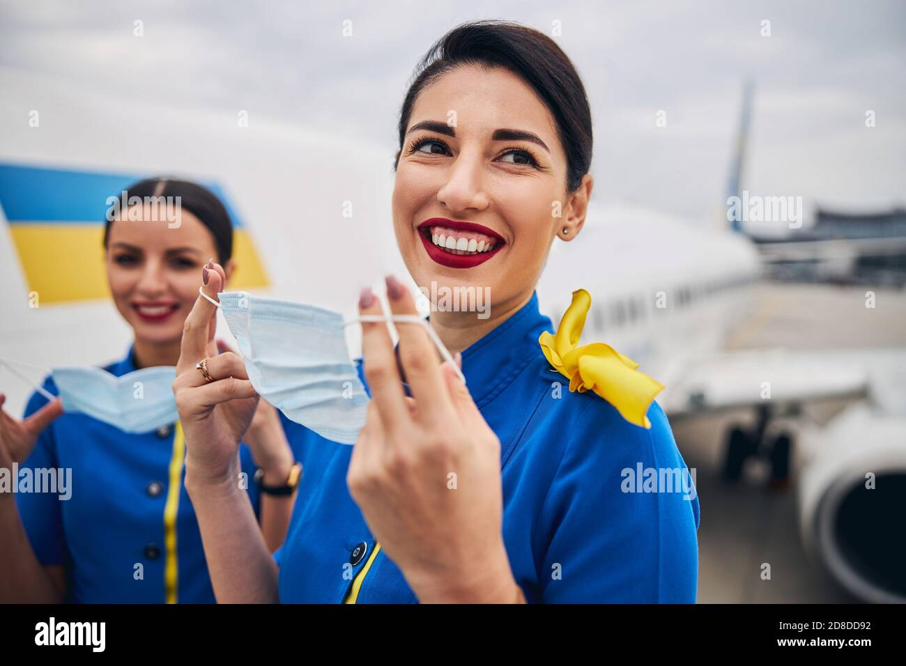 Two stewardesses holding face coverings in their hands Stock Photo