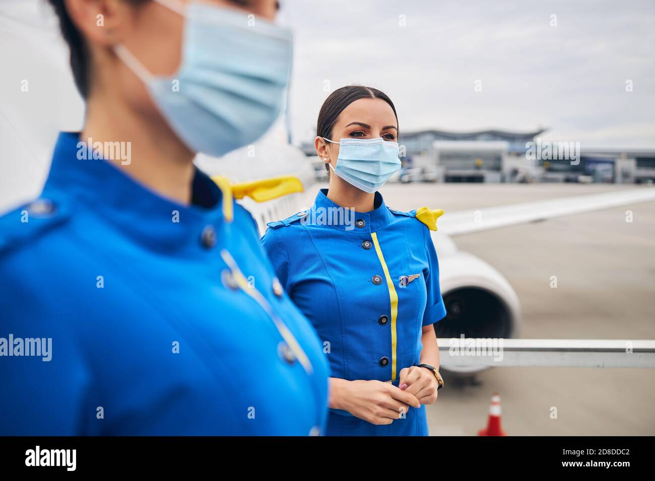 Dreamy young stewardesses in face coverings at the airdrome Stock Photo