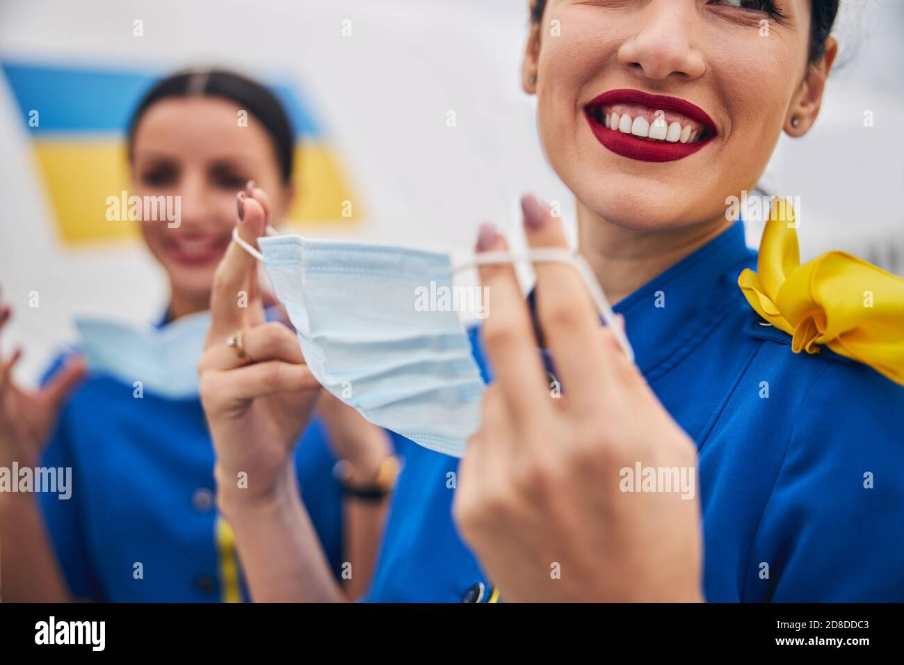 Two young flight attendants putting on face coverings Stock Photo