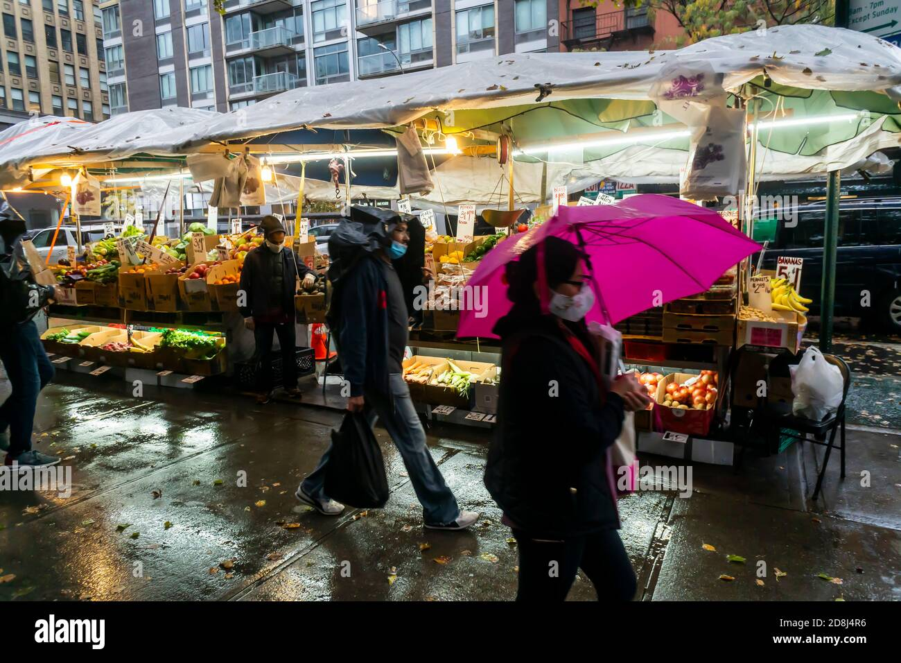 Customers at a fruit stand in the Chelsea neighborhood of New York suffering the remnants of Hurricane Zeta on Thursday, October 29, 2020. Thursday saw steady rain all day continuing into Friday with a drop in temperatures predicted for the weekend. Yikes! (© Richard B. Levine) Stock Photo