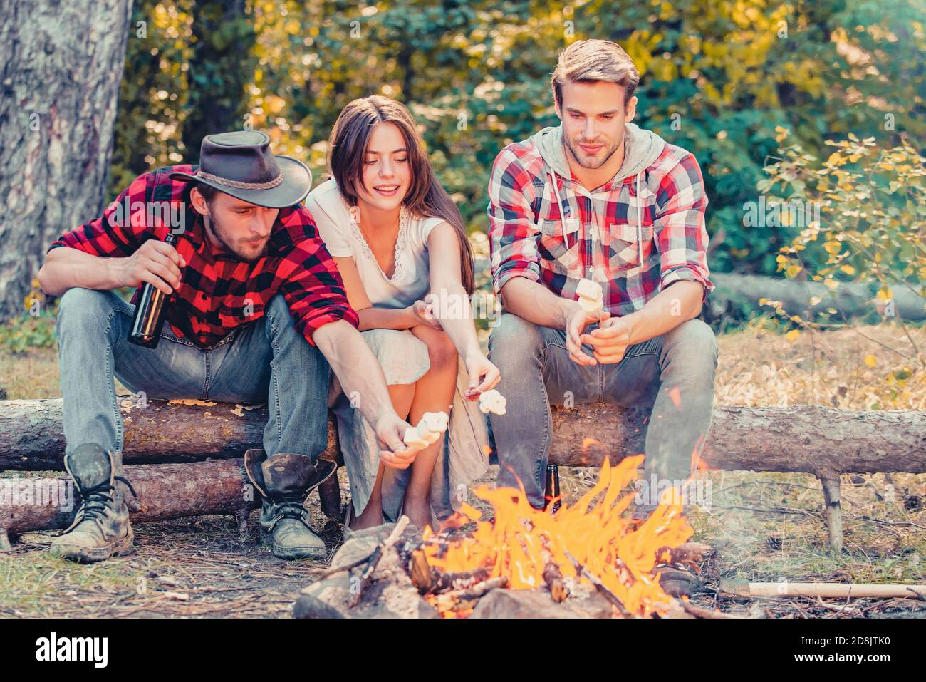 Happy young friends having picnic. Group of friends enjoying picnic in the forest. Happy friends on a camping trip relaxing by campfire. Company Stock Photo