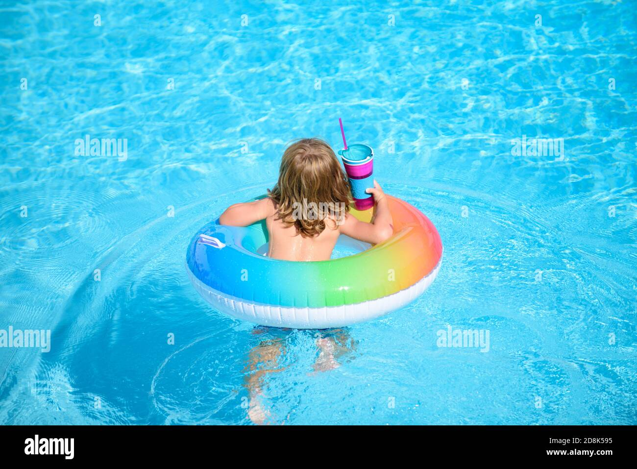 Kid with colorful swim ring in swimming pool on summer day. Water toys and floats for child. Healthy sport for children. Family beach vacation. Stock Photo