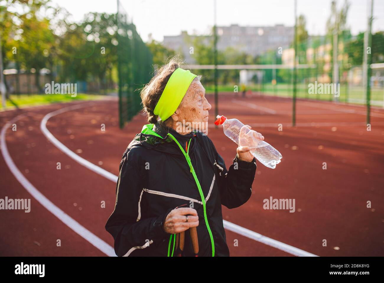 Age maturity, active lifestyle and wellness. Joyful retired woman with walking poles and bottle of water, refreshing during physical activity. Elderly Stock Photo