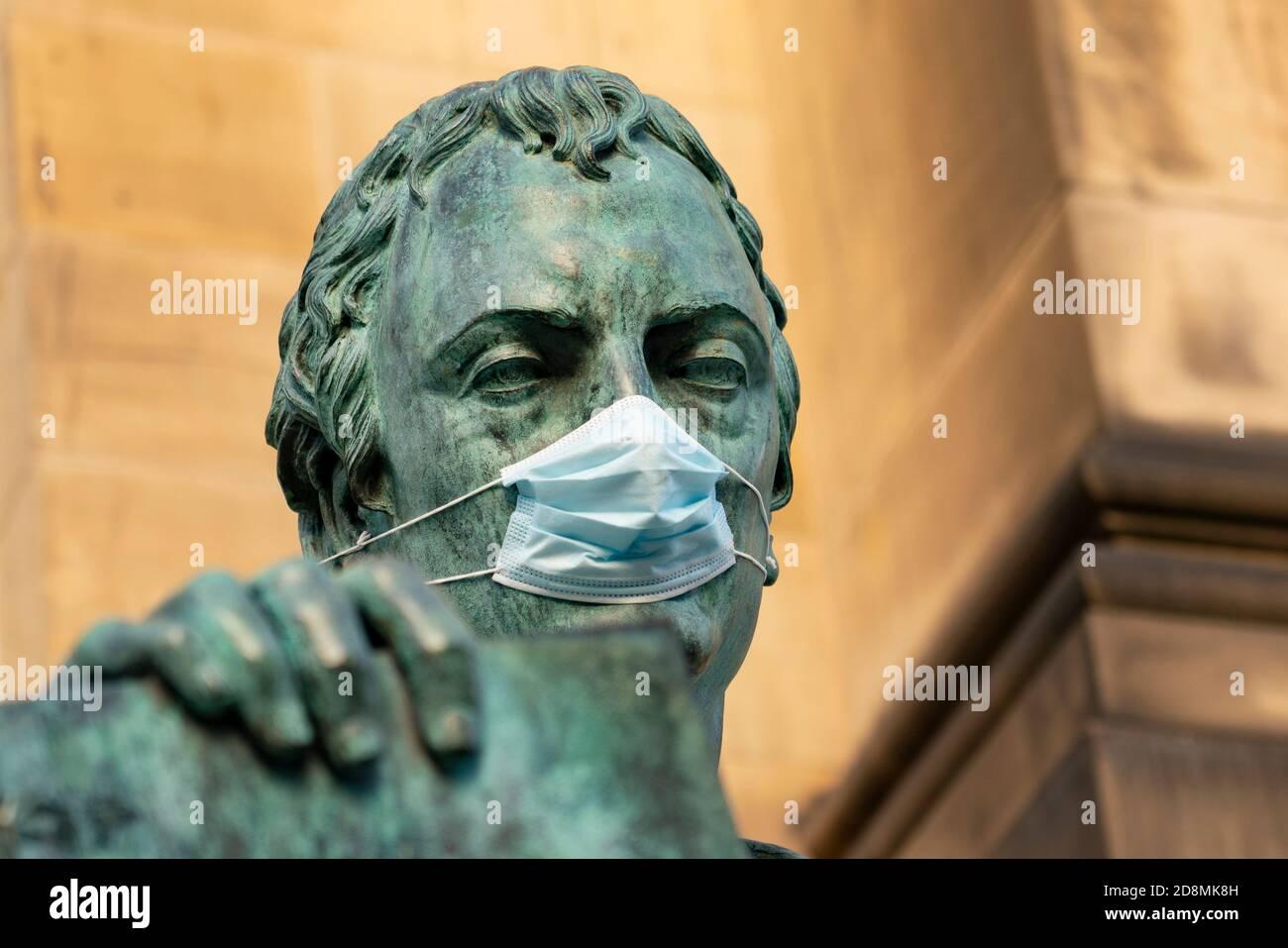 Statue of David Hume philosopher wearing facemask  on Royal Mile in Edinburgh, Scotland, UK Stock Photo