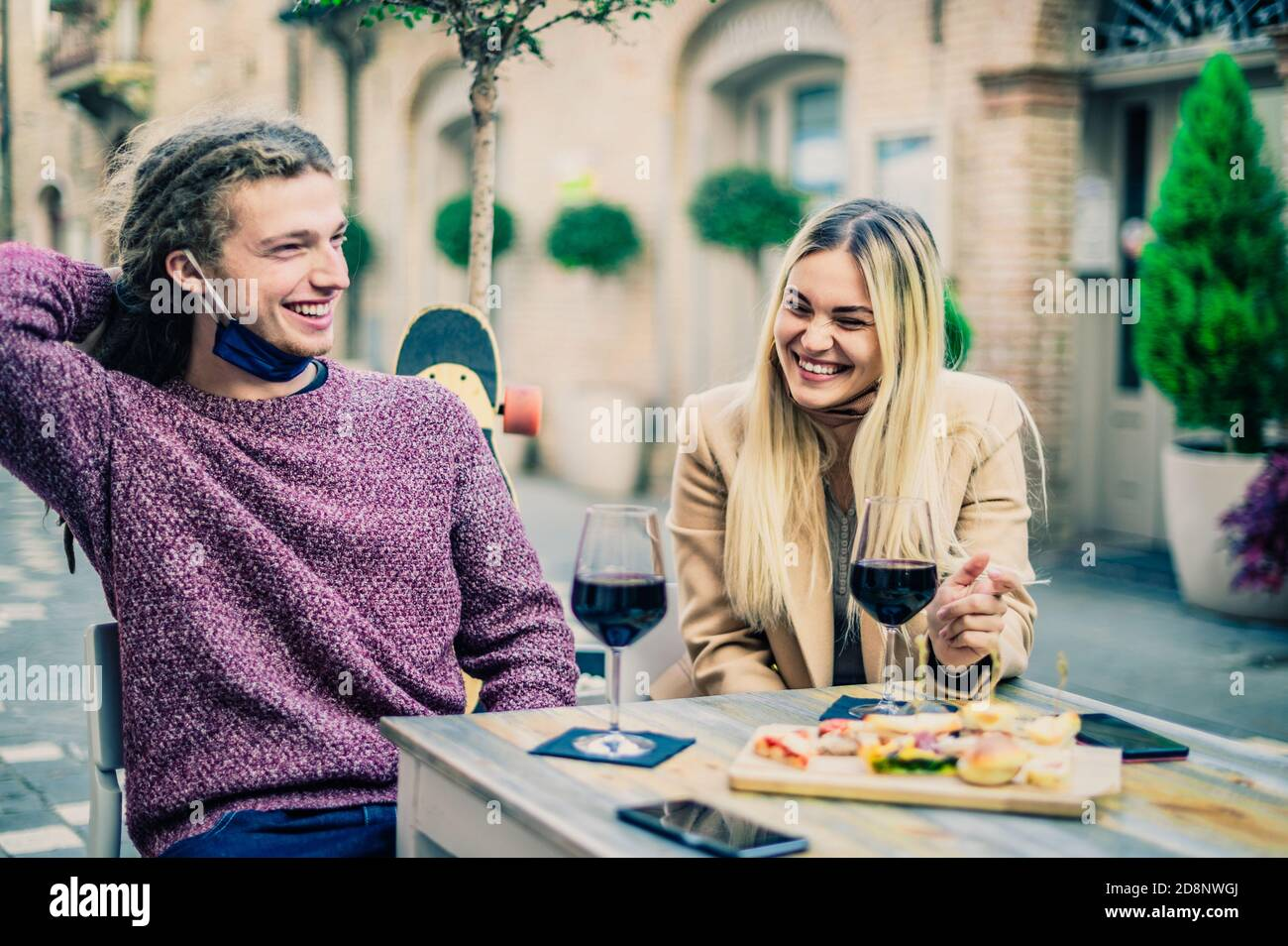 Couple drinking red wine at bar with open face masks in coronavirus time - New normal concept - Focus on women Stock Photo