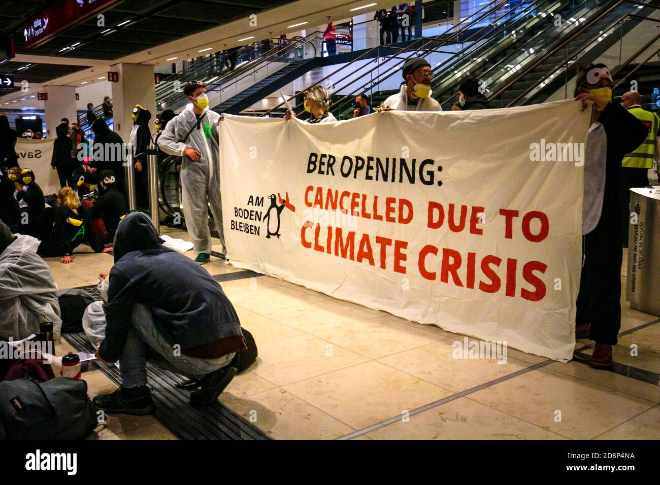 """Climate activists hold """"BER opening: cancelled due to climate crisis"""" sign to protest the opening of Berlin Brandenburg International Airport (BER). Stock Photo"""