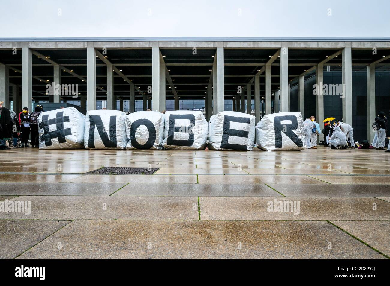 """""""#NOBER"""" is spelled out as climate activitists in penguin costumes protest the opening of new Berlin Brandenburg International (BER) Airport. Stock Photo"""
