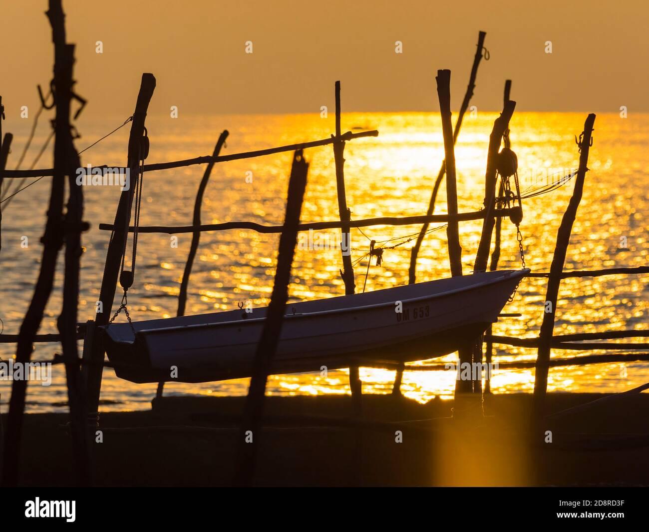 Intensive vivid sunset setting sun Yellow featuring hanging silhouette boat o wooden posts Basanija near Savudrija, Istria Coast in Croatia Europe Stock Photo