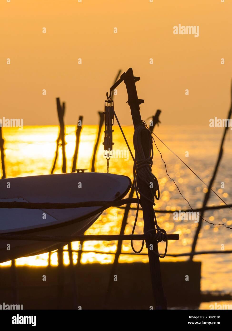 Intensive vivid sunset setting sun Yellow featuring hanging silhouette boat om wooden posts Basanija near Savudrija, Istria Coast in Croatia Europe Stock Photo