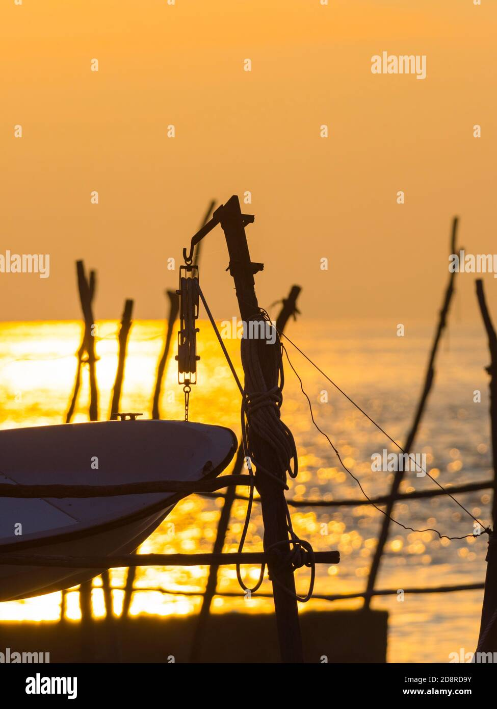 Intensive vivid sunset setting sun Yellow featuring hanging silhouette boat bow wooden post Basanija near Savudrija, Istria Coast in Croatia Europe Stock Photo