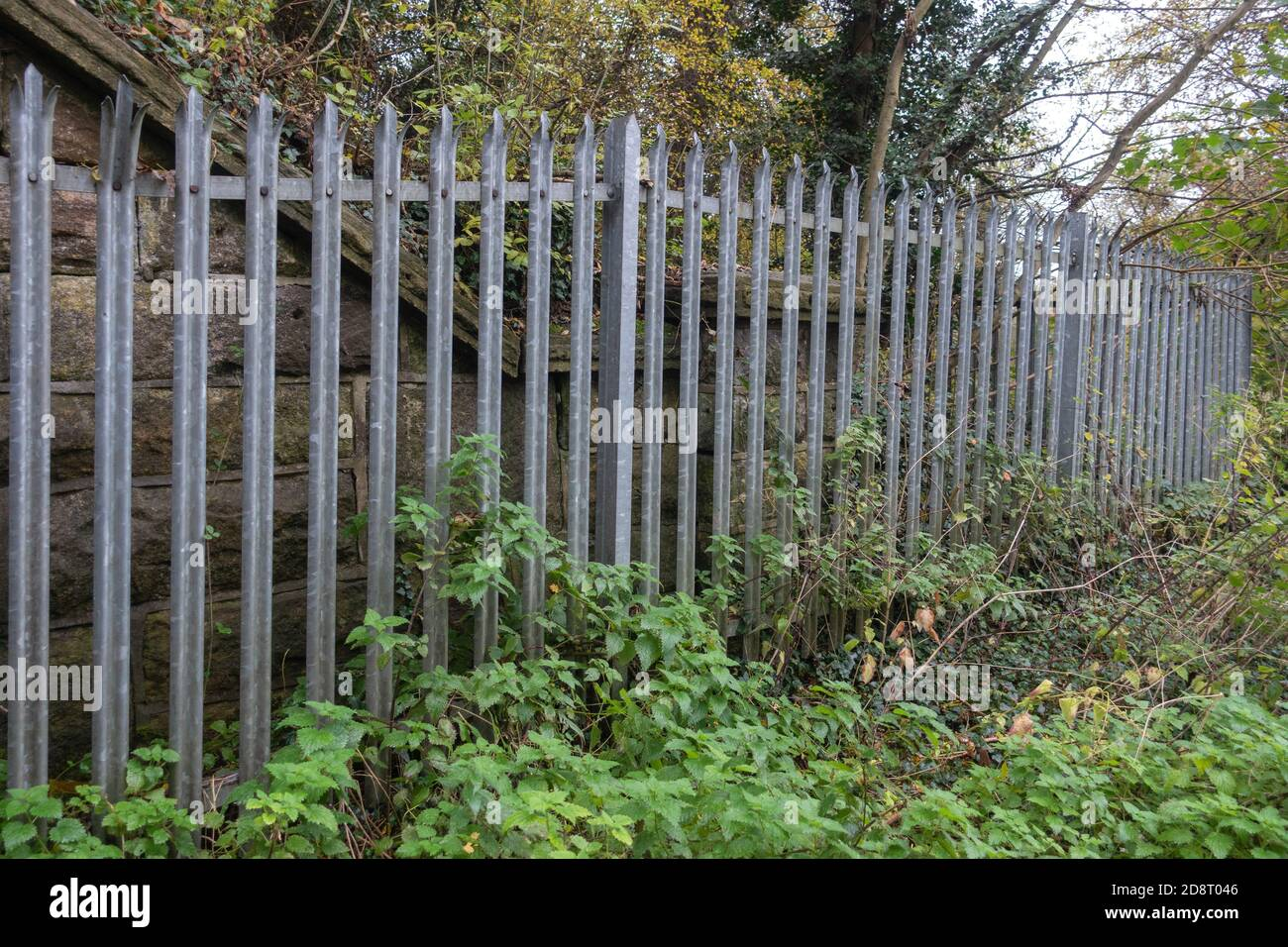 Galvanised steel palisade spiked security fencing on railway banks Stock Photo