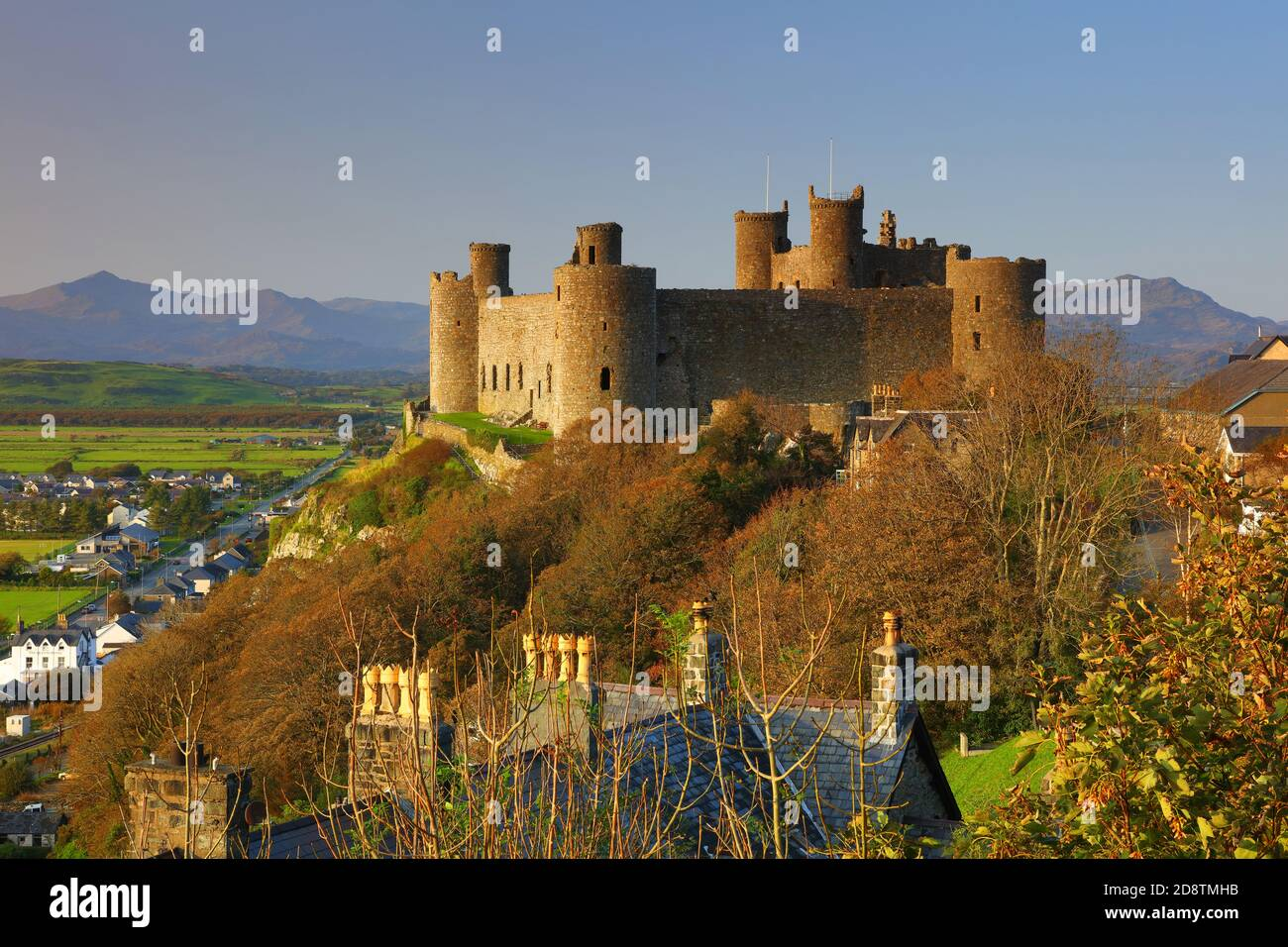 Harlech Castle in late evening sunlight and blue sky with mountains in the distance, Snowdonia, North Wales, UK. Stock Photo