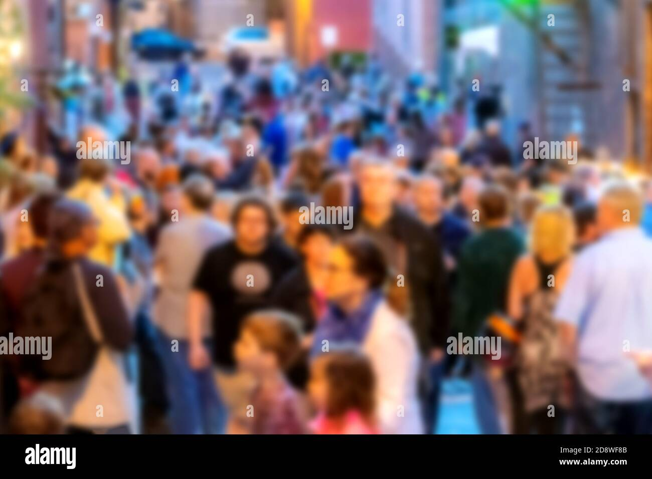 A blur of a crowd of people at dusk. People are gathered on a street between buildings. People are blurred enough not to be recognizable. Stock Photo