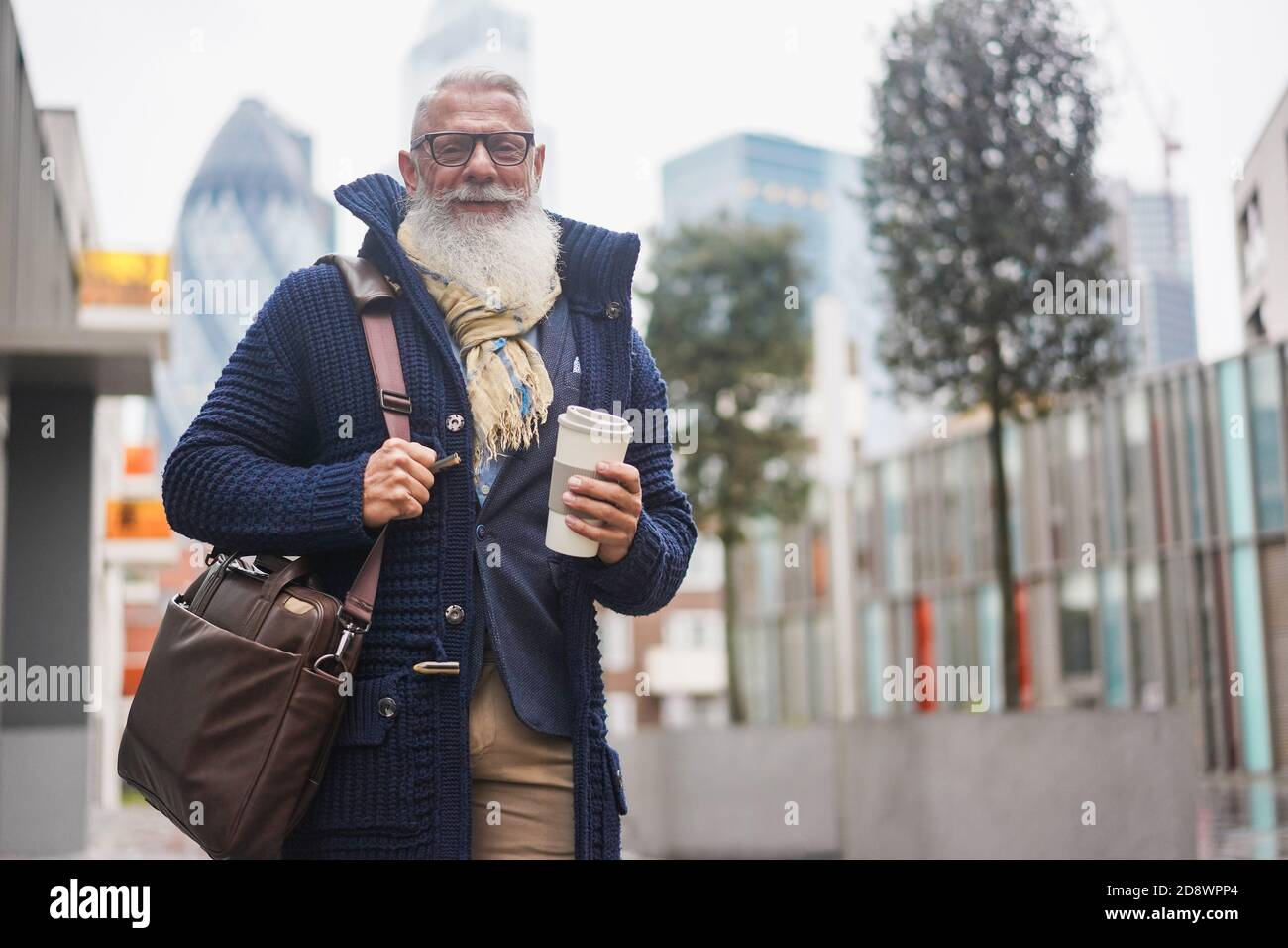 Senior hipster businessman drinking coffee in the city on winter day - Focus on face Stock Photo