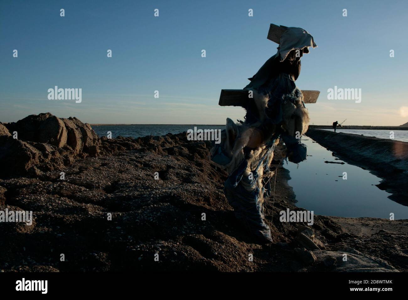 The scarecrow of Sfax saline with sunset winter and blue sky reflection on water. Tunisia Stock Photo