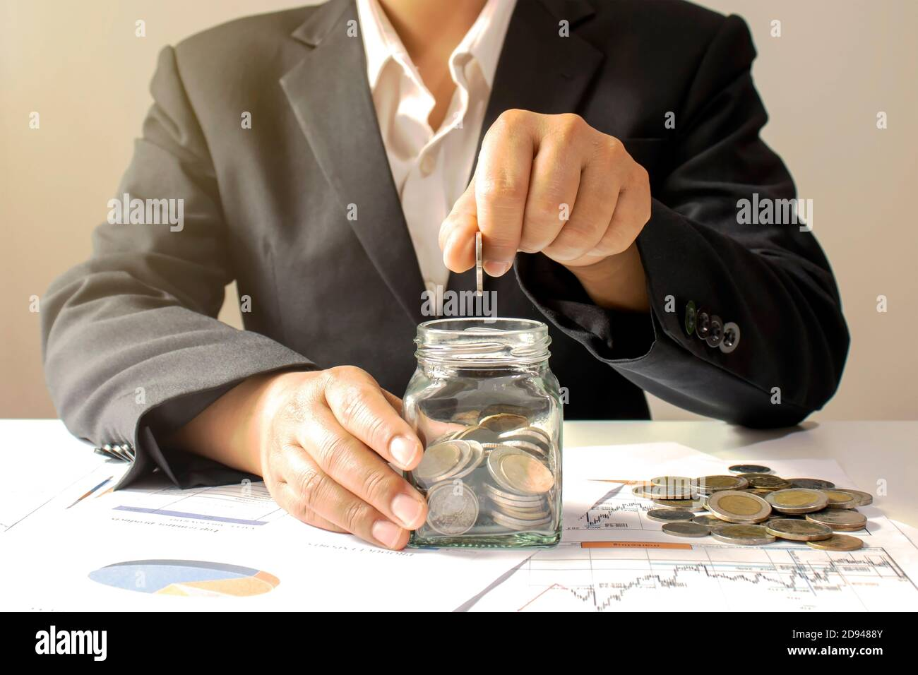 Business Woman Holding A Coin In A Money Jar And Window Light Money Saving Idea Stock Photo Alamy