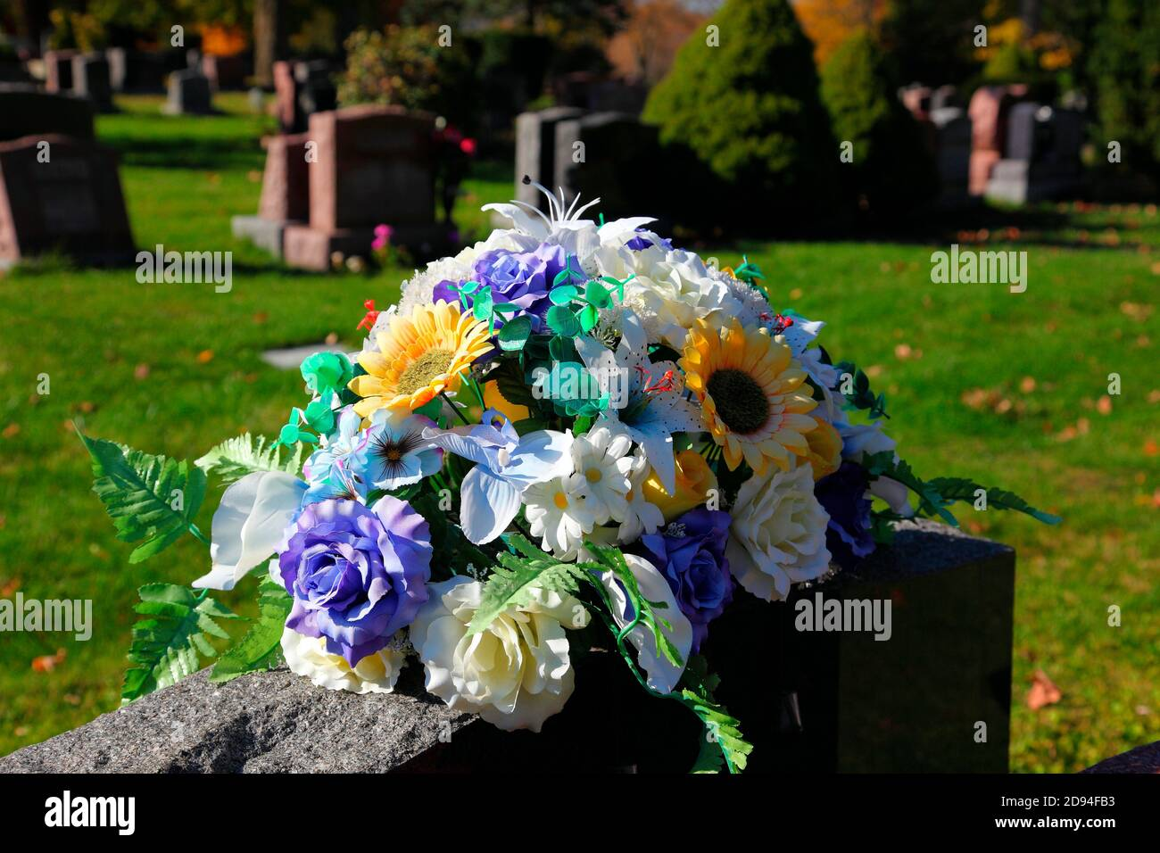 flowers on a grave stone Stock Photo