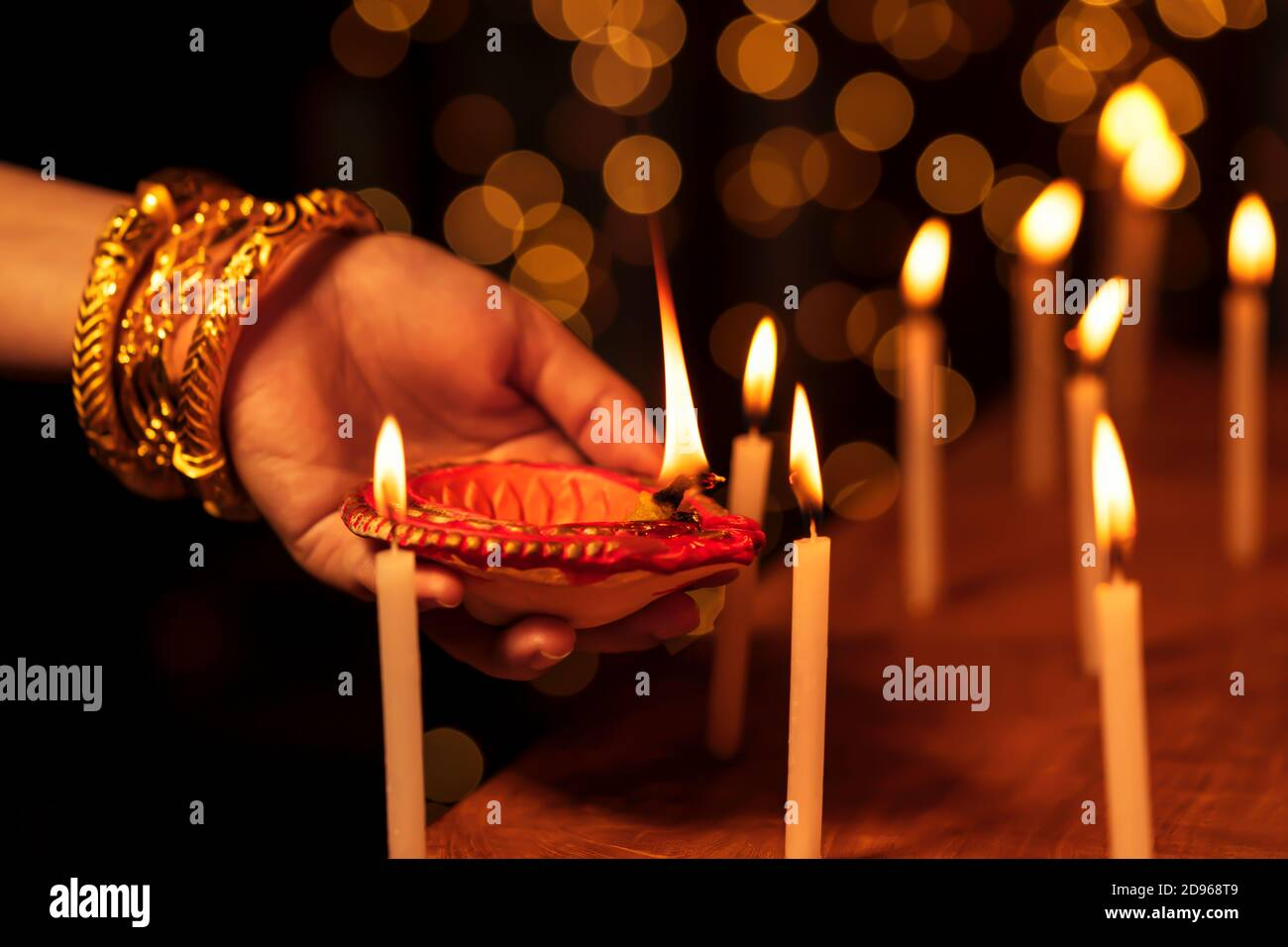 Indian housewife or bride woman wearing traditional gold jewelry, lighting candles with a clay diya or oil lamp in one hand at a temple on Diwali nigh Stock Photo
