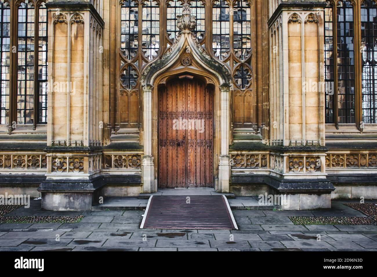 Oxford, UK - March 02 2020: Exterior of the Divinity School in Oxford showing a big wooden door entrance and columns and stained glass windows Stock Photo