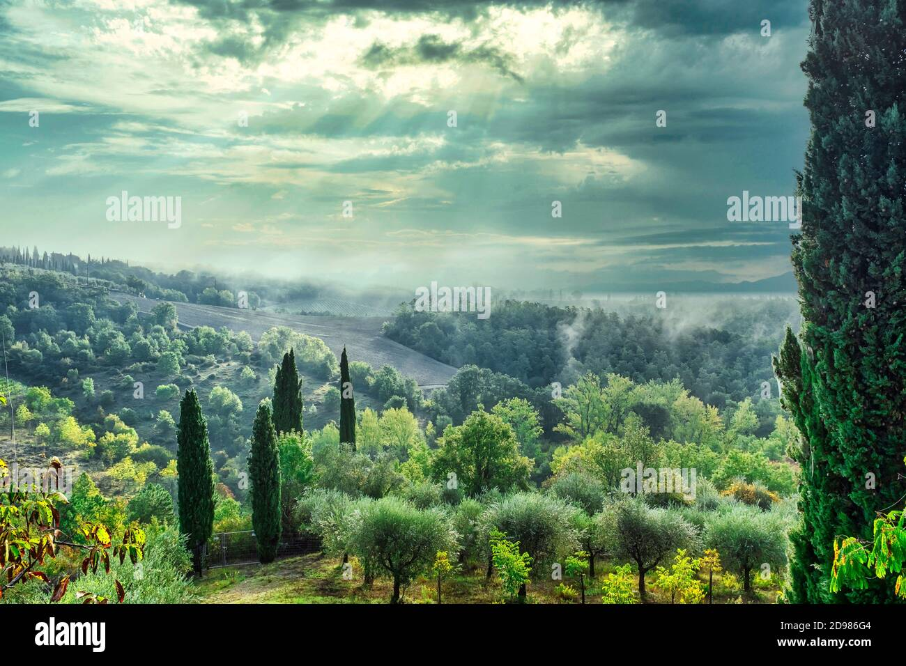 Picturesque green countryside in Tuscany Italy with sun shining through clouds. Stock Photo