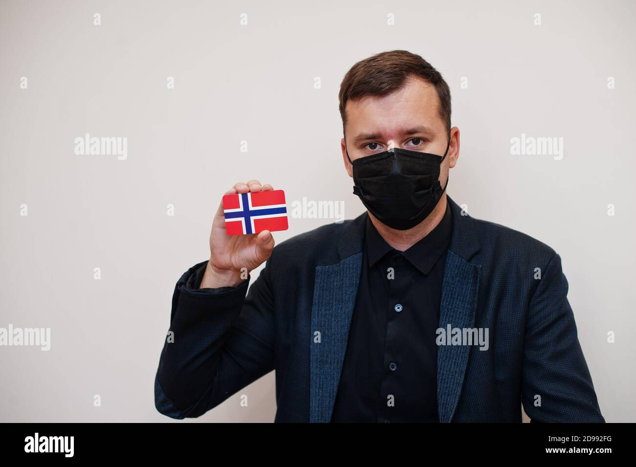 European man wear black formal and protect face mask, hold Norway flag card isolated on white background. Europe coronavirus Covid country concept. Stock Photo
