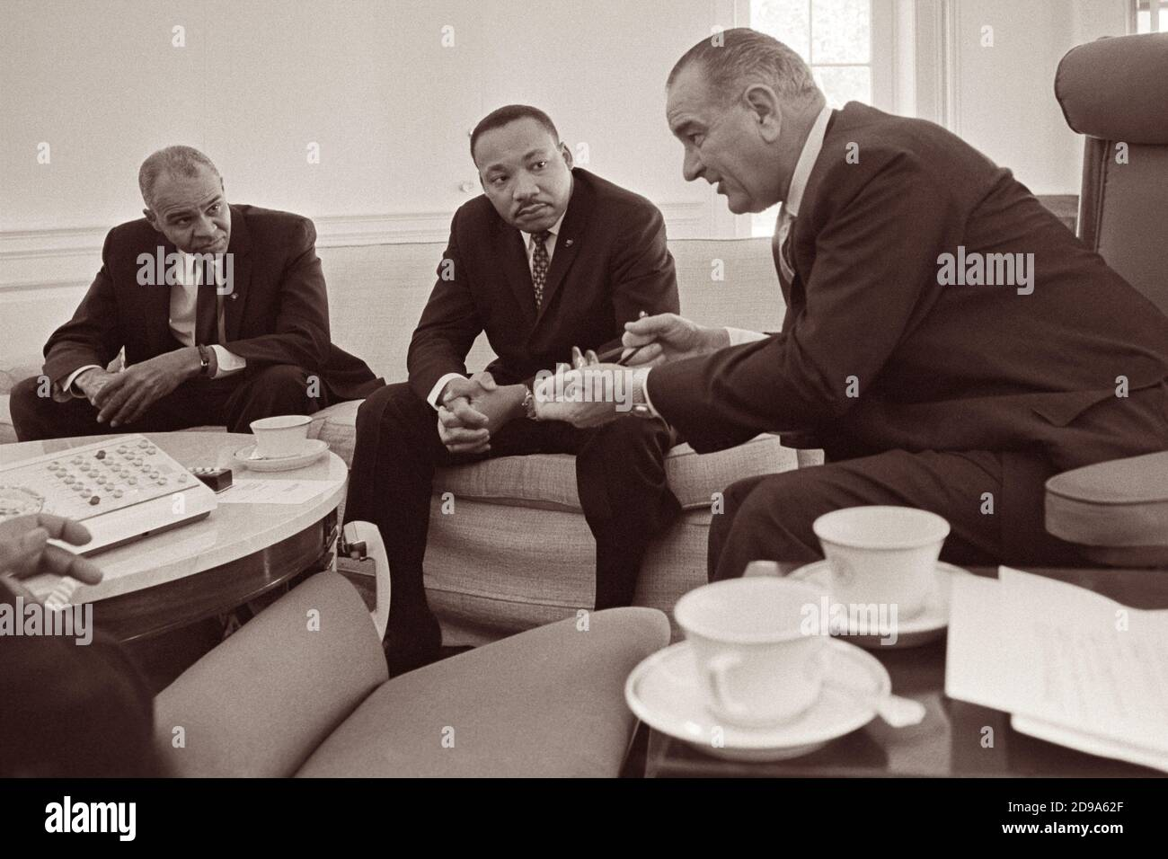 Roy Wilkins and Dr. Martin Luther King, Jr. meet with President Lyndon B. Johnson in the Oval Office of the White House on January 18, 1964. Stock Photo