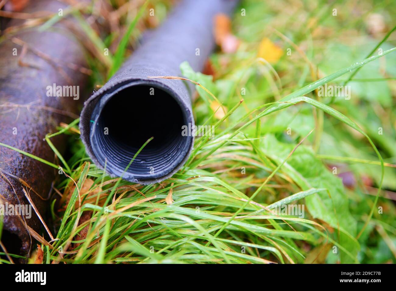 Close-up of black plastic pipes with geotextile lying on the grass Stock Photo