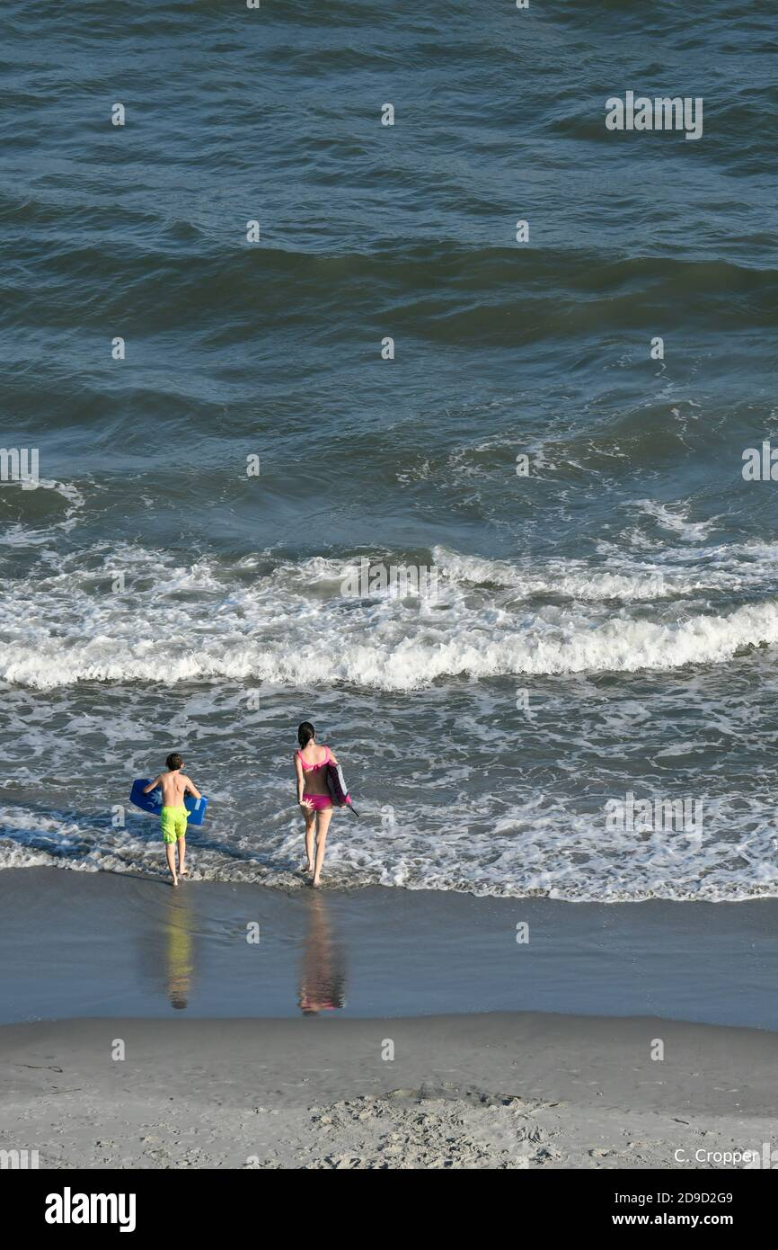Kids on the beach walking into ocean with flotation devices Stock Photo