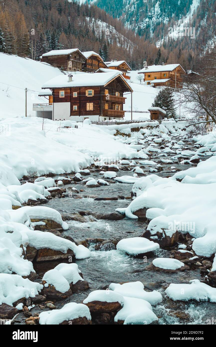 Ice and snow covered creek on a cold winter day infront of traditional wooden cabins of little mountain village St. Gertraud in Ultental, South Tyrol/ Stock Photo