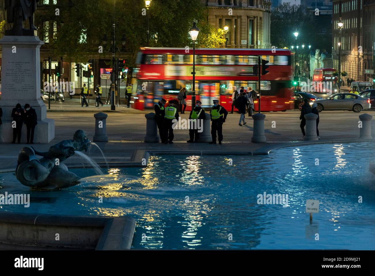 Police patrolling Trafalgar Square in preparation for an anti lockdown protest on the first day of the second COVID-19 lockdown, London, UK. Evening Stock Photo