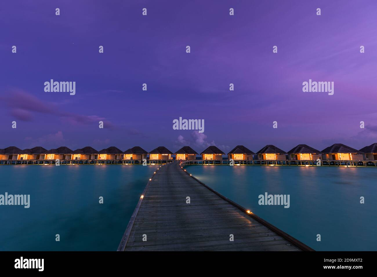 Overwater bungalows in Maldives islands. Tropical paradise island destination, led lights with long jetty under twilight night sky. Exotic landscape Stock Photo