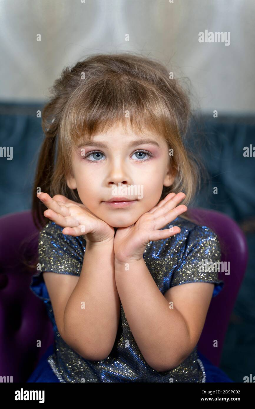 portrait of a beautiful little girl in a blue dress with makeup. professional makeup for children Stock Photo