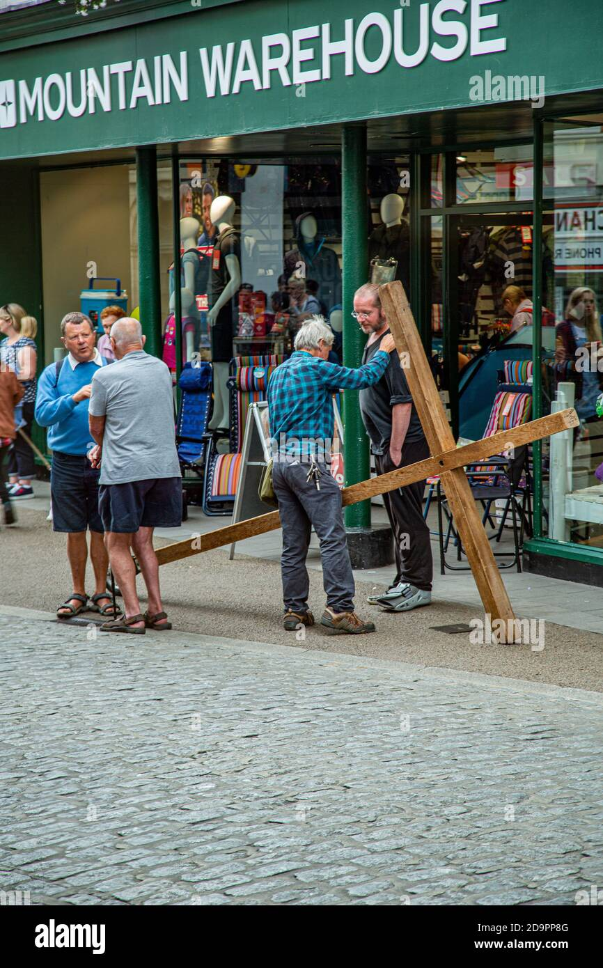 Carrying a wooden cross through the streets and shoppers. Stock Photo