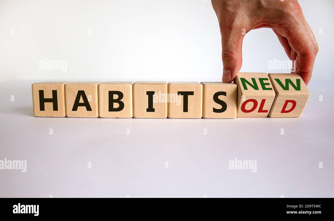 Male hand turning a cube and changes the expression 'old habits' to 'new habits'. Beautiful white table, white background. Concept. Copy space. Stock Photo