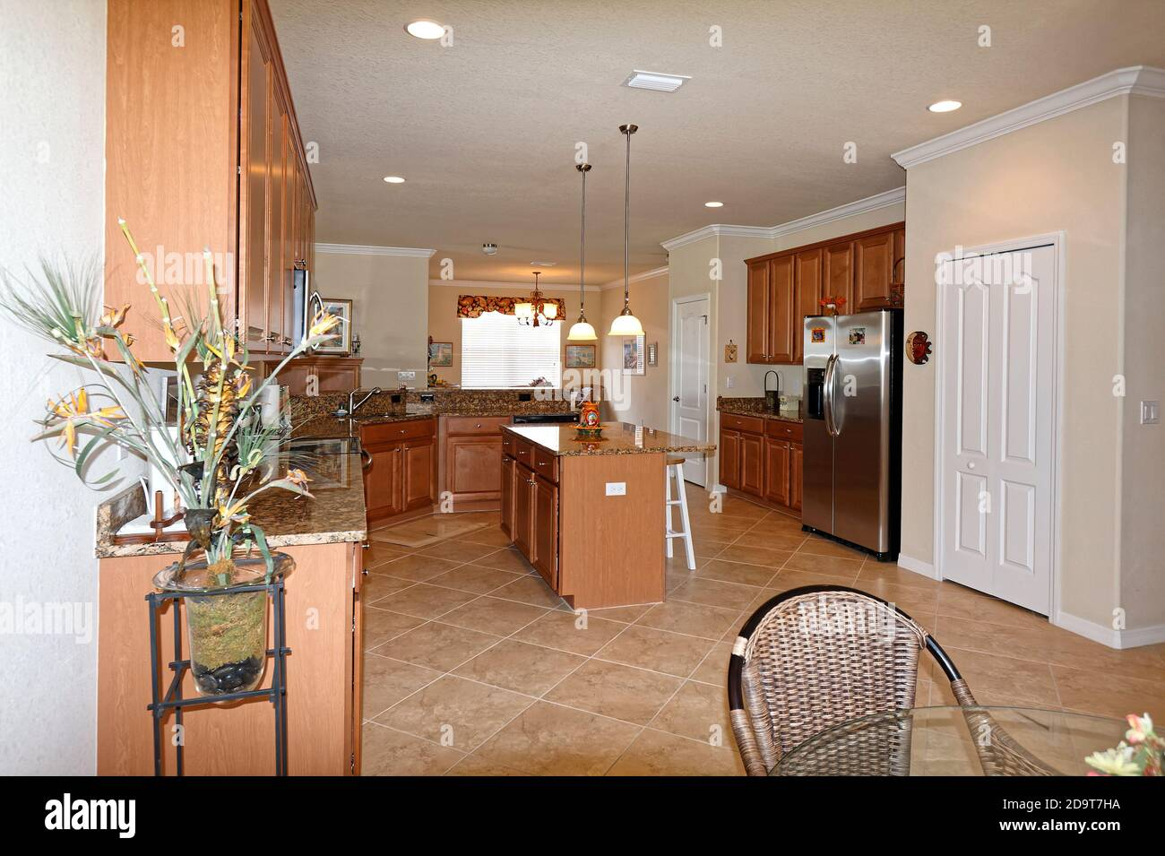 large modern kitchen, granite counters, center island, wood cabinets, recessed lighting, hanging lights, tile floor, set on diagonal, window, valance, Stock Photo