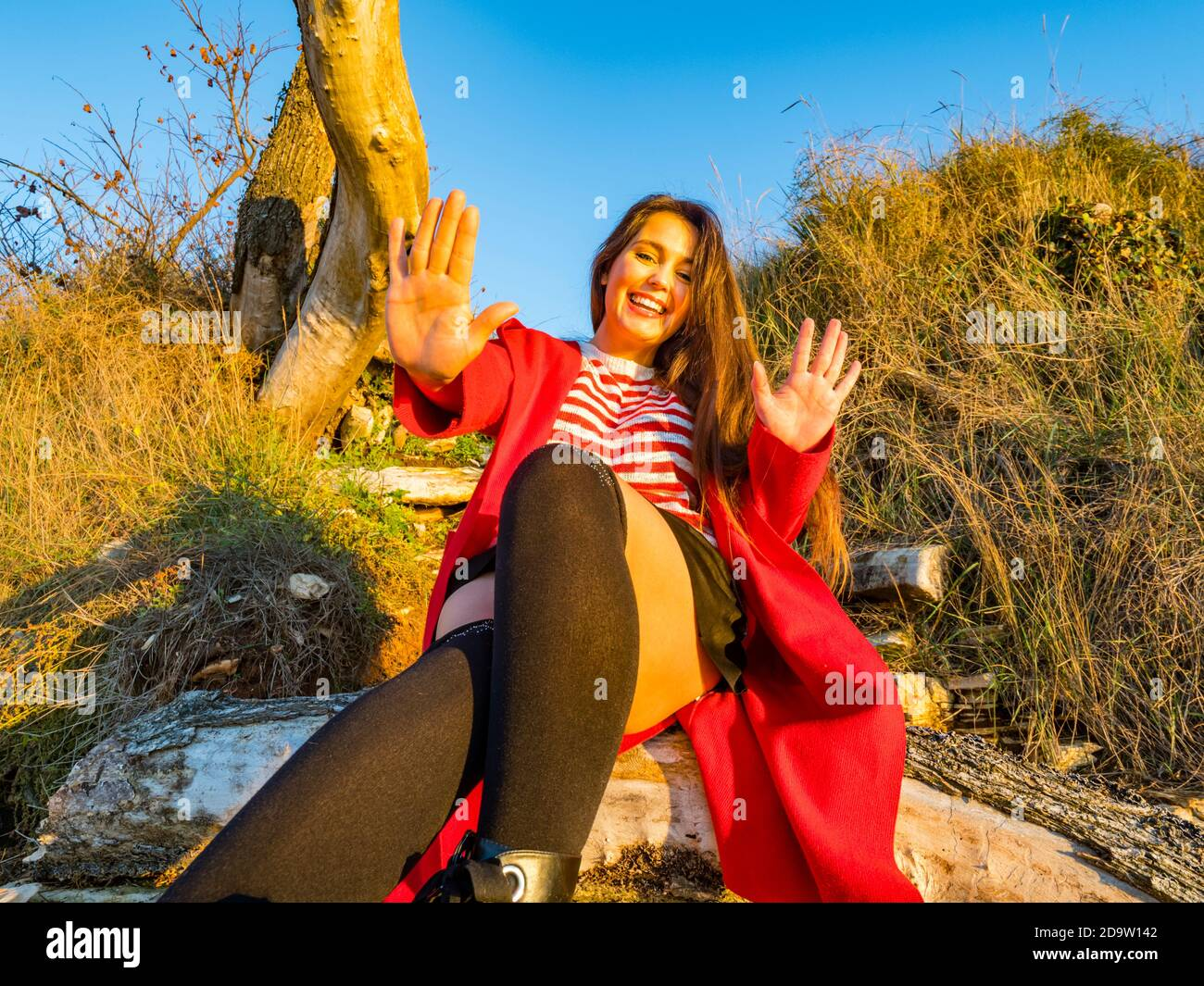Young woman sitting seated looking at camera happy smiling wants to stop stopping denial deny refusing defensive cute Stock Photo