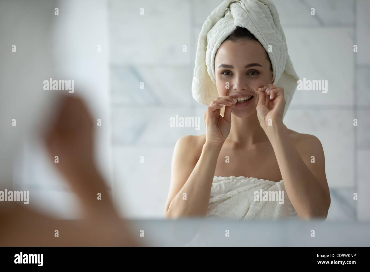 Pleasant lady cleaning teeth with dental floss after morning shower Stock Photo