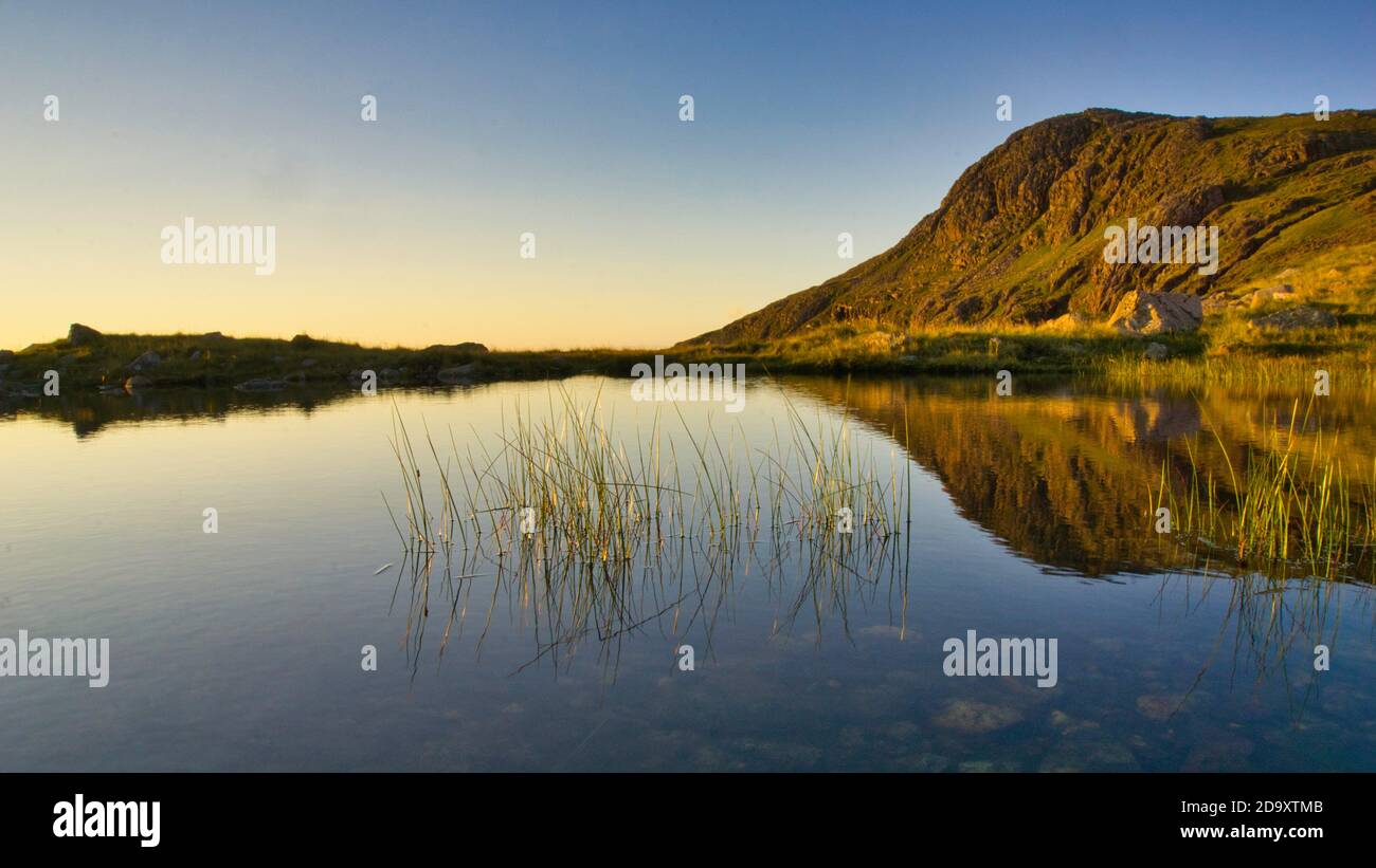 Mountains reflection: reflections of Bow Fell in a tarn , Langdale Valley, Lake District Stock Photo