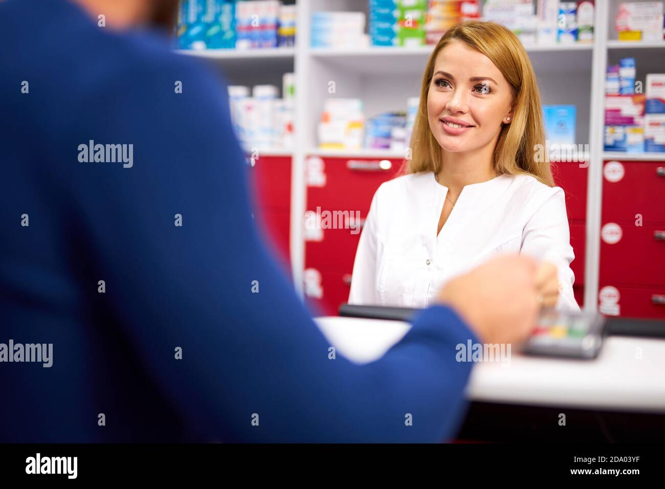 young beautiful caucasian pharmacist is working with customer in modern drugstore, serve the client, wearing white medical gown Stock Photo