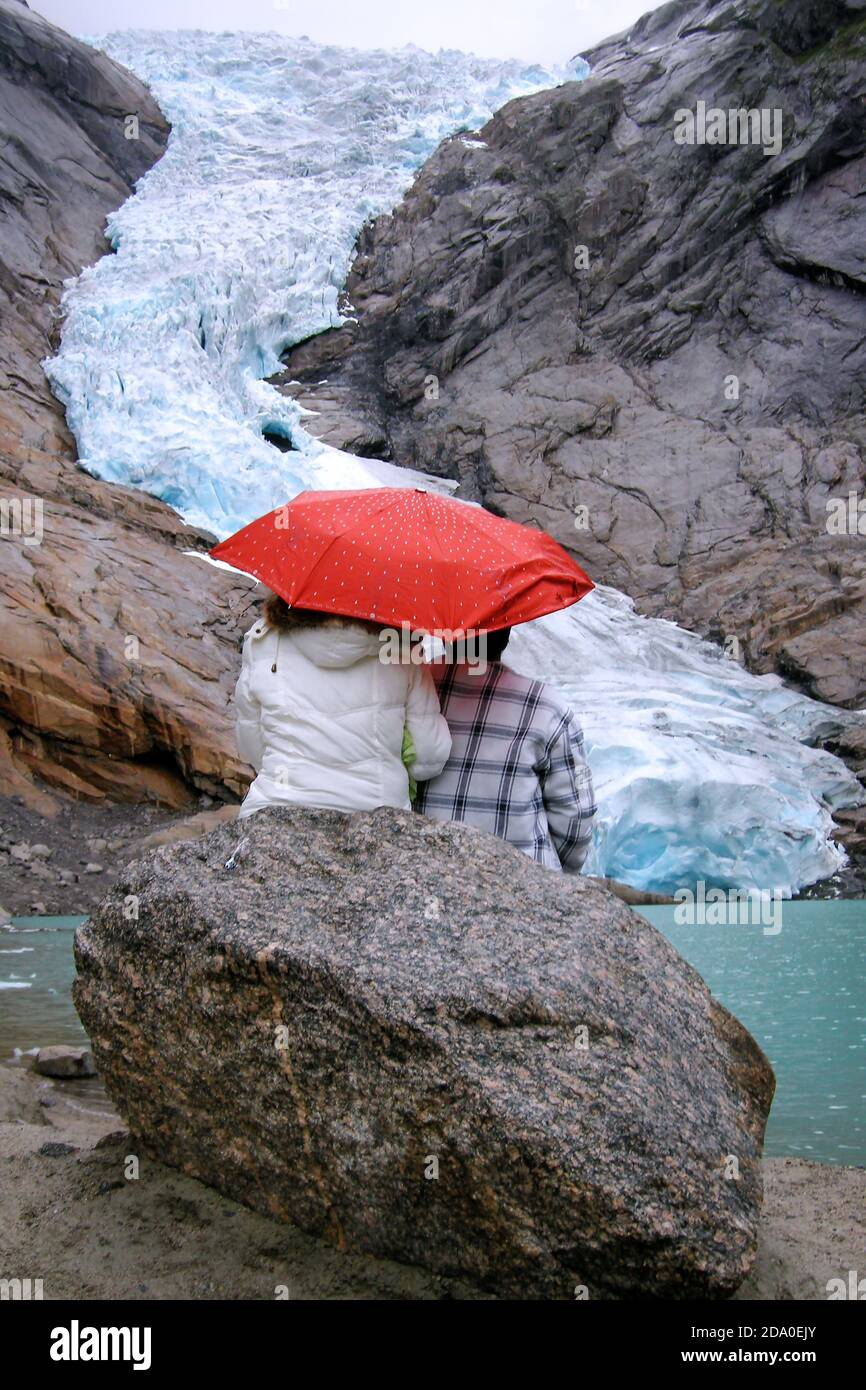 Briksdal Glacier (Briksdalbreen), Norway. Couple with an umbrella sitting on a rock looking at Briskdal Glacier. View of the glacier 10 years ago. Stock Photo